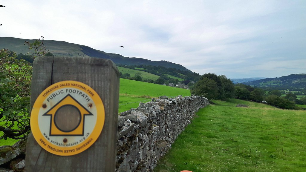 public footpath sign with stone wall and green hills in the background.