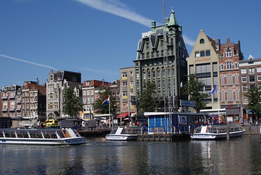 Constructions du 19e siècle dominant Damrak, l'avenue reliant la gare et la place centrale de Dam.