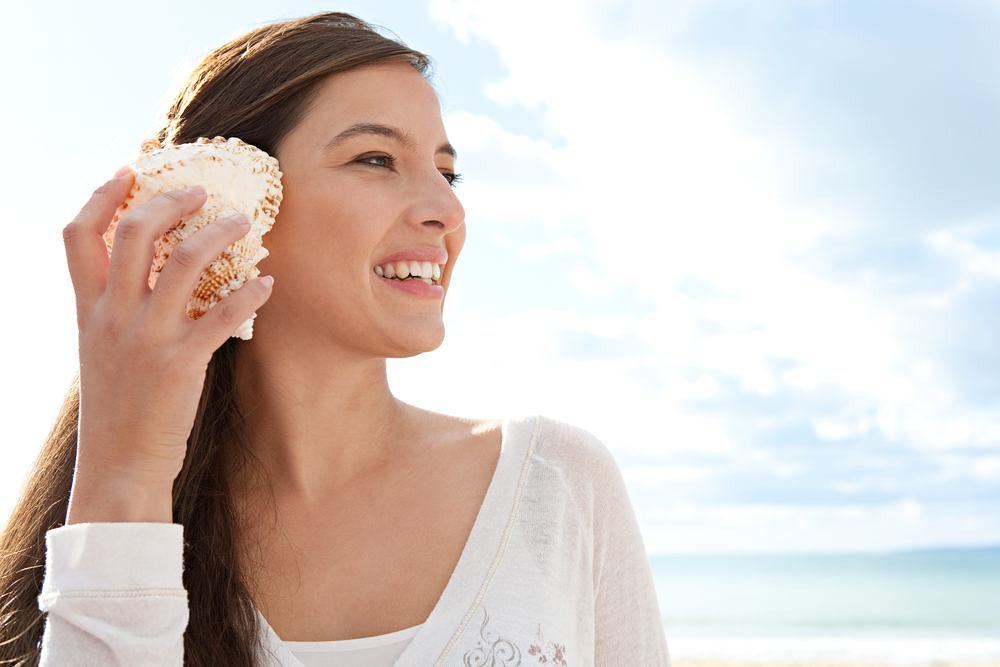 woman holding seashell to her ear and smiling