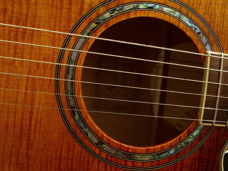 close-up photo of acoustic guitar sound hole and rosette