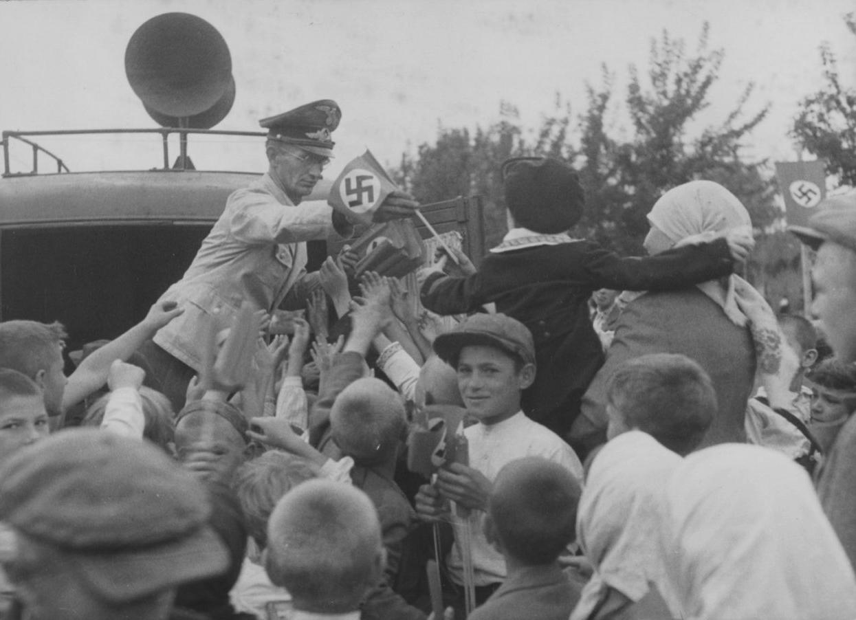 1943. Сотрудник рейхсминистерства оккупированных восточных территорий раздает флажки со свастикой жителям Киева