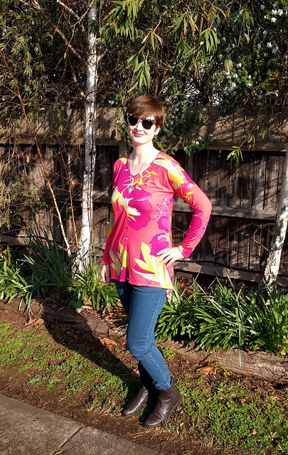 A woman wears a tropical floral print long sleeve top and jeans.