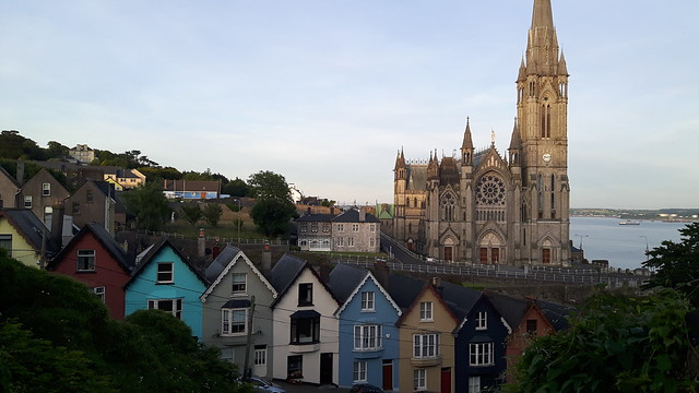 Row of colourful houses with a cathedral behind in Cobh, Ireland
