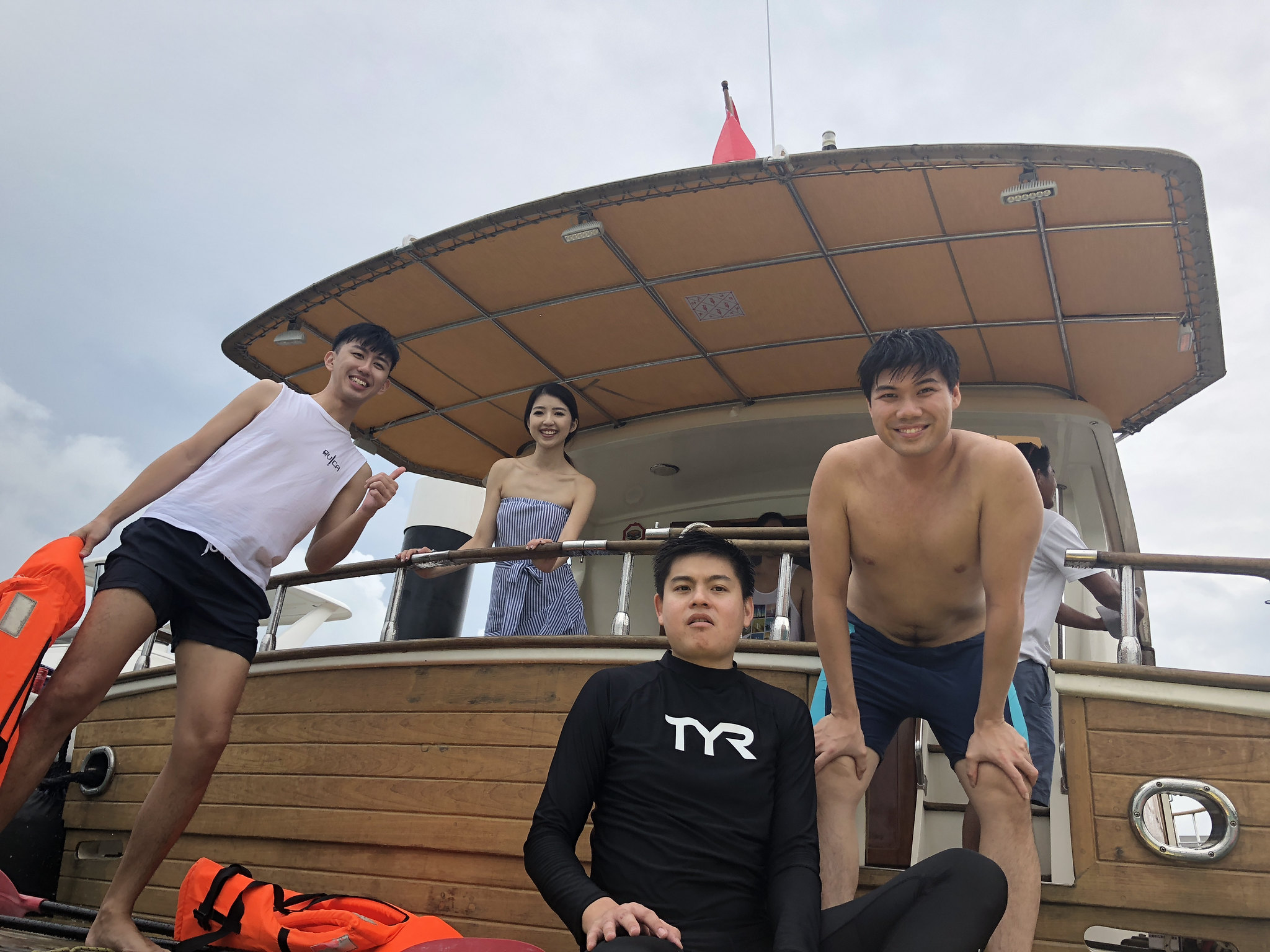 Happy friends on the Yacht while playing some water activities!
