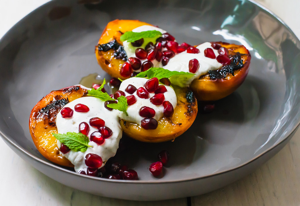 This simple summer dessert recipe is the epitome of summer. Charred peaches topped with with tangy vanilla speckled labneh and topped with honey and pomegranate seeds.