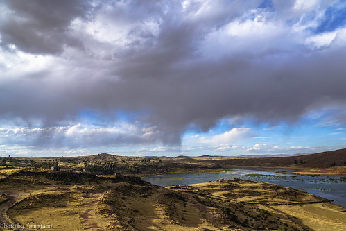 travel peru andes mountains landscape nature altiplano sillustani lake umayo water sky cloud field grass ancient architecture building