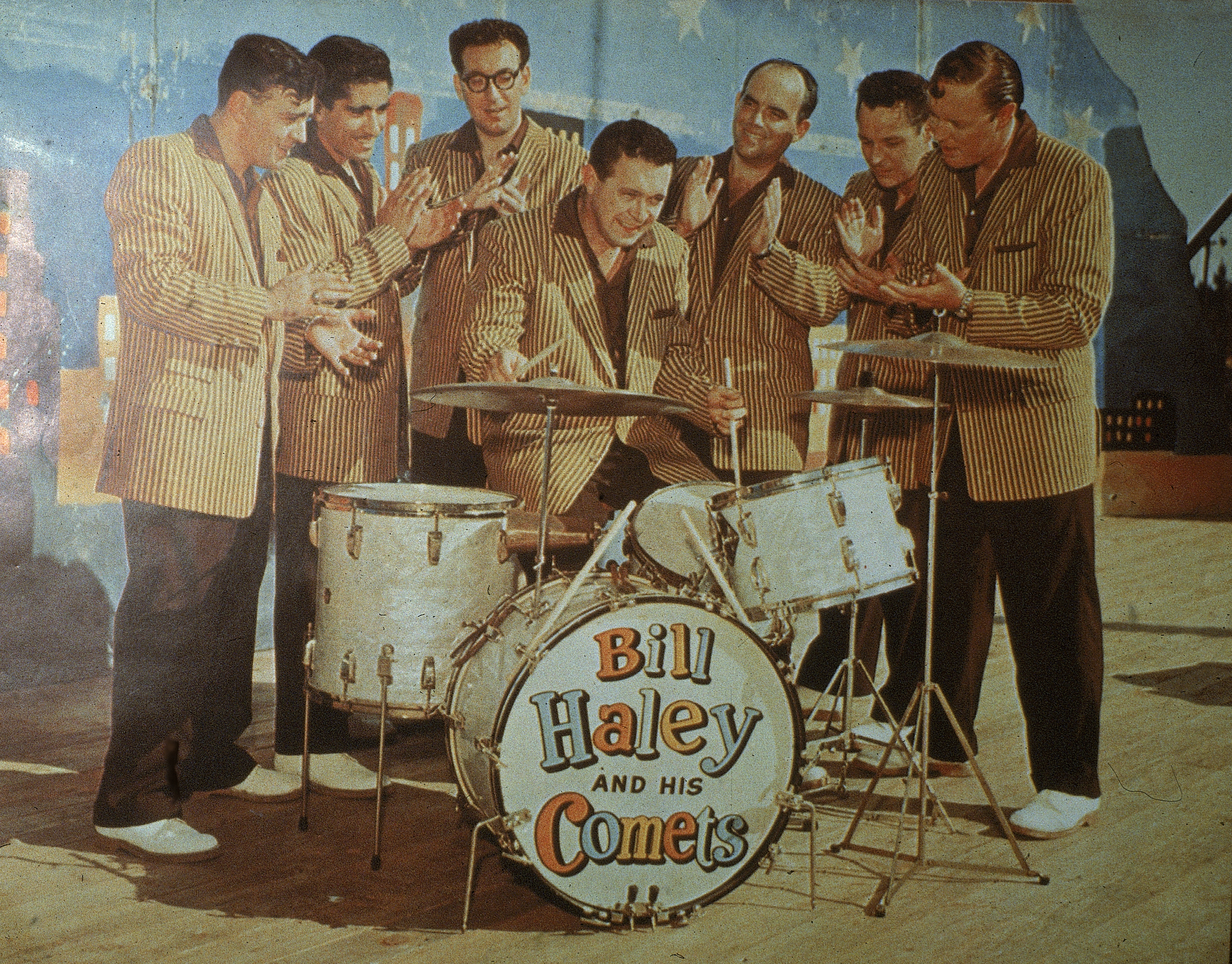 Promotional portrait of American rock and roll band Bill Haley & His Comets as they wear matching jackets, black pants, and white shoes, January 1957. Group leader Bill Haley (1925 - 1981) sits in the center playing the drums. (Photo by Hulton Archive/Getty Images)