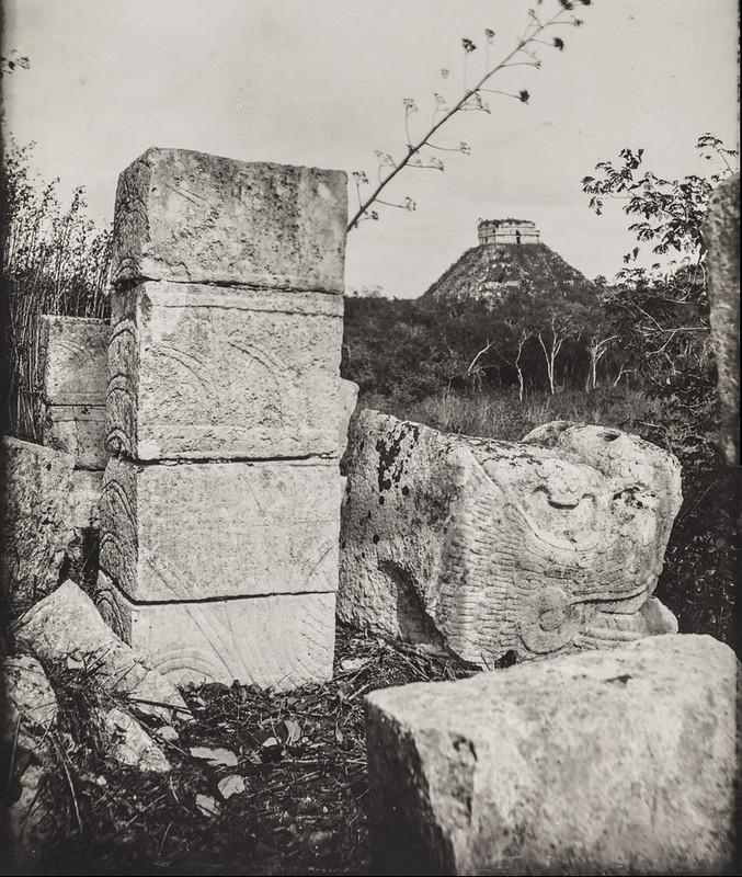 Чичен-Ица. Каменная скульптура пернатого змея и рельефные камни. На заднем плане - пирамида Кукулькан