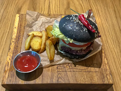 Veg Kuro Burger at Avocado Cafe: lentil and cereal patty, blackened bun made with use of charcoal, peanut sauce, tomatoes, pickles, lettuce leaves, chilli pepper