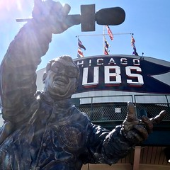 "Harry Caray statue IS the C in ""Chicago Cubs"" Sign —under the flags at Wrigley Field."