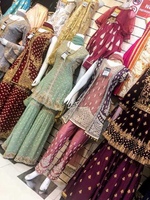 A row of colorful red, green and gold South Asian clothing along a shop wall.