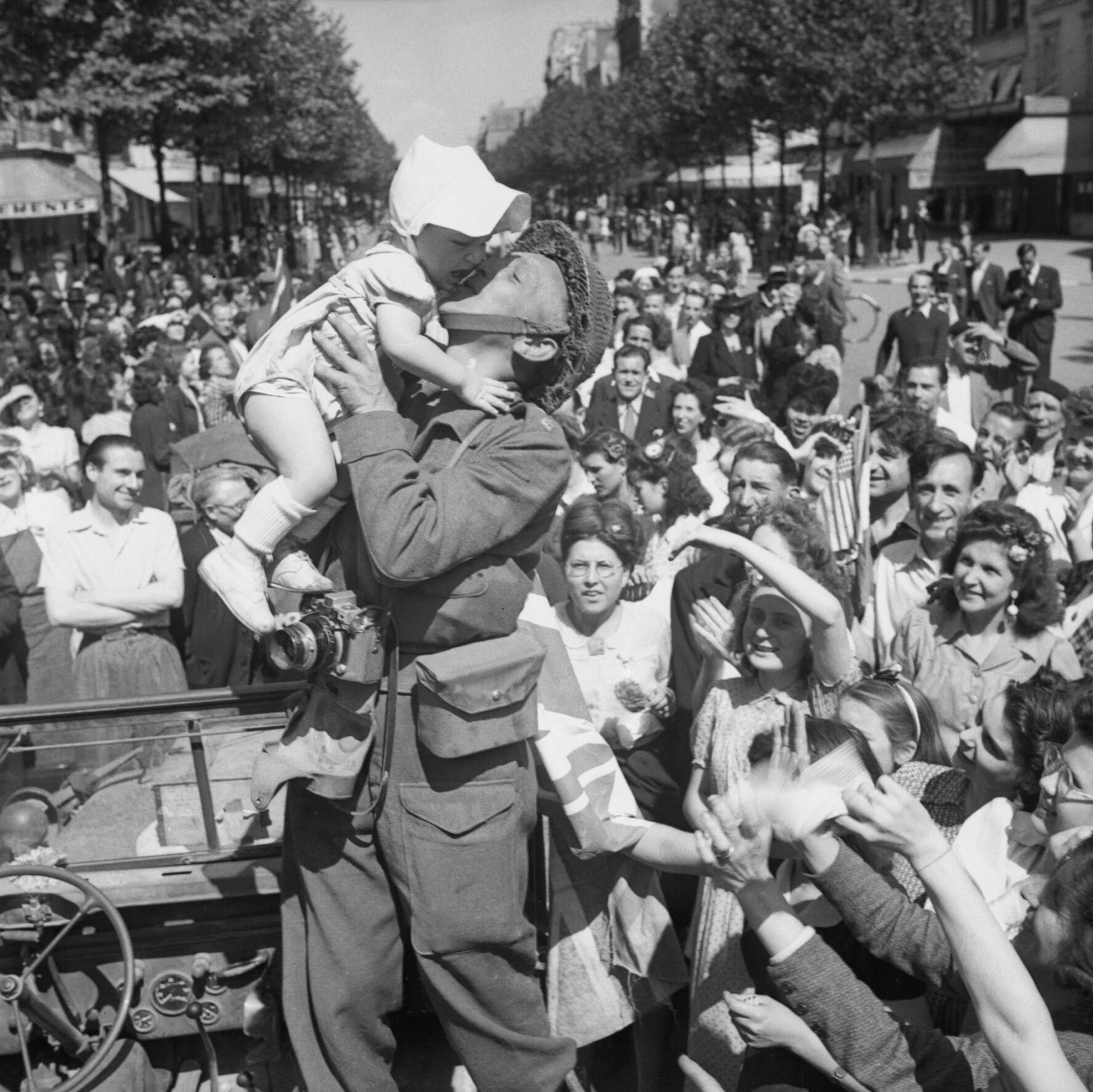 An AFPU photographer kisses a small child before cheering crowds in Paris, August 26, 1944. Photo taken by Captain E. G. Malindine,, No 5 Army Film & Photographic Unit. From the collections of the Imperial War Museums.