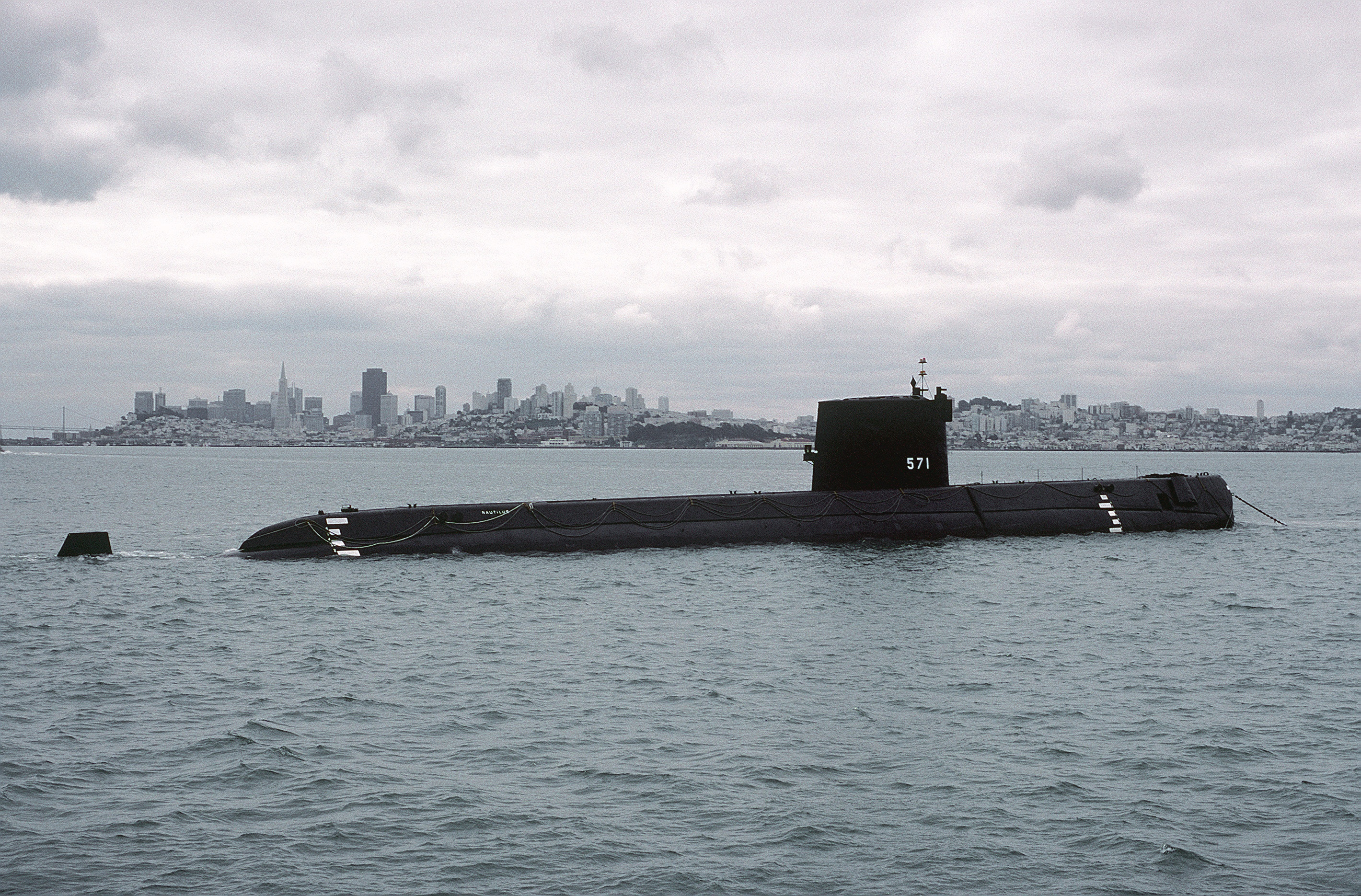 A starboard side view of the nuclear-powered attack submarine ex-USS Nautilus (SSN 571) with the city of San Francisco visible in the background. The Nautilus was being towed from Naval Shipyard Mare Island to Groton, Connecticut, where it became a museum.