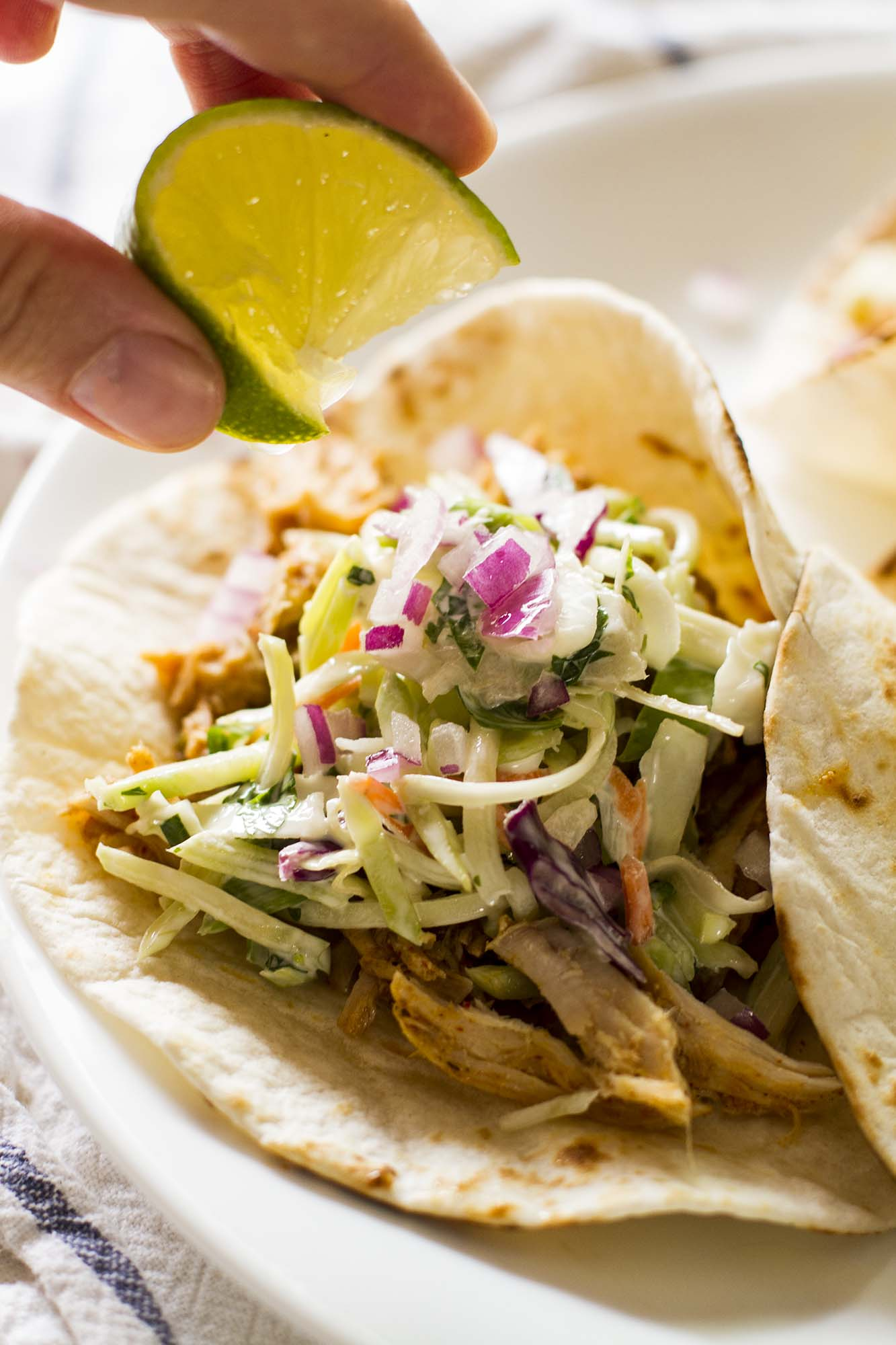 Slow Cooker Green Chile Pork Tacos with Cilantro-Lime Slaw! So easy and yet so much flavor. These will be your new go-to taco night meal! #easydinner #taconight #slowcooker #crockpot @girlversusdough #girlversusdough