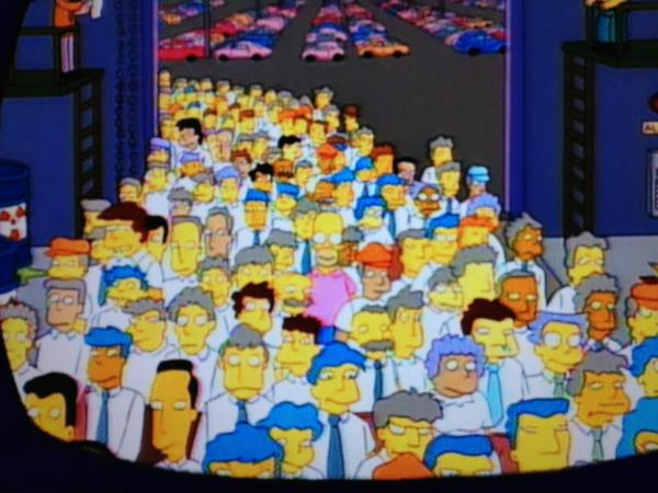 Homer Simpson in a pink shirt coming into work in a crowd of a people, being watched on CCTV