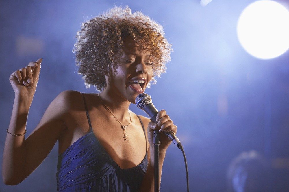 woman singing passionately into a microphone at a nightclub
