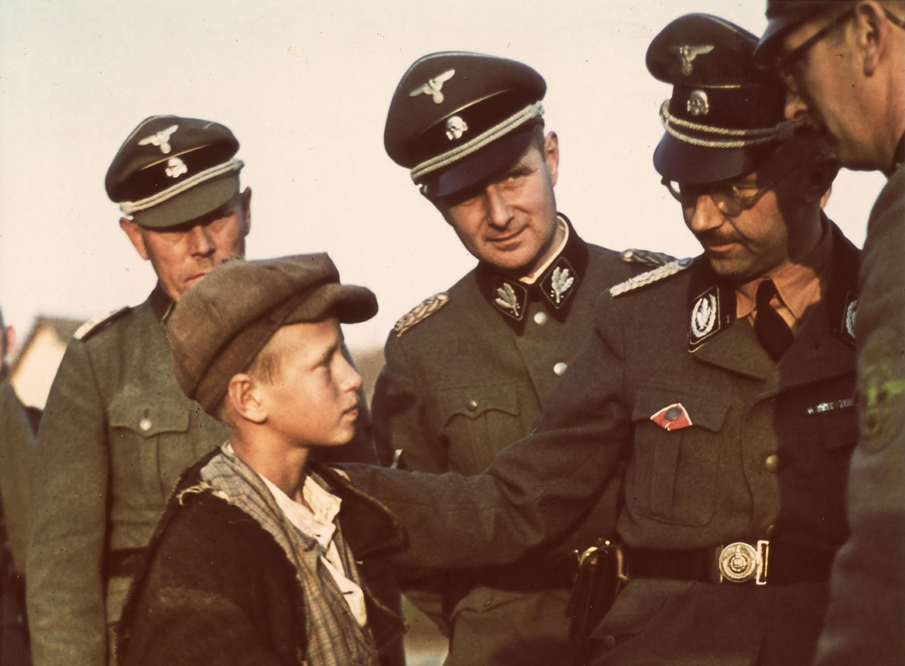 1941. Рейхсфюрер СС Генрих Гиммлер разговаривает с мальчиком из местных жителей во время инспекционной поездки по Белоруссии.  Этот и еще один мальчик были отправлены в детский дом в Германию