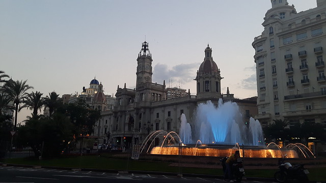 A lit fountain with beautiful buildings behind in a plaza in Valencia, Spain