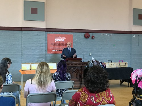 Troy Mayor Patrick Madden speaks while standing at a podium facing an audience. An orange banner hangs on the wall behind the mayor features the mission of the YWCA