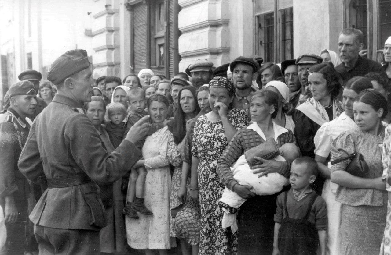 1941. Немецкий офицер обращается к стоящим в очереди местным жителям в оккупированном Могилеве