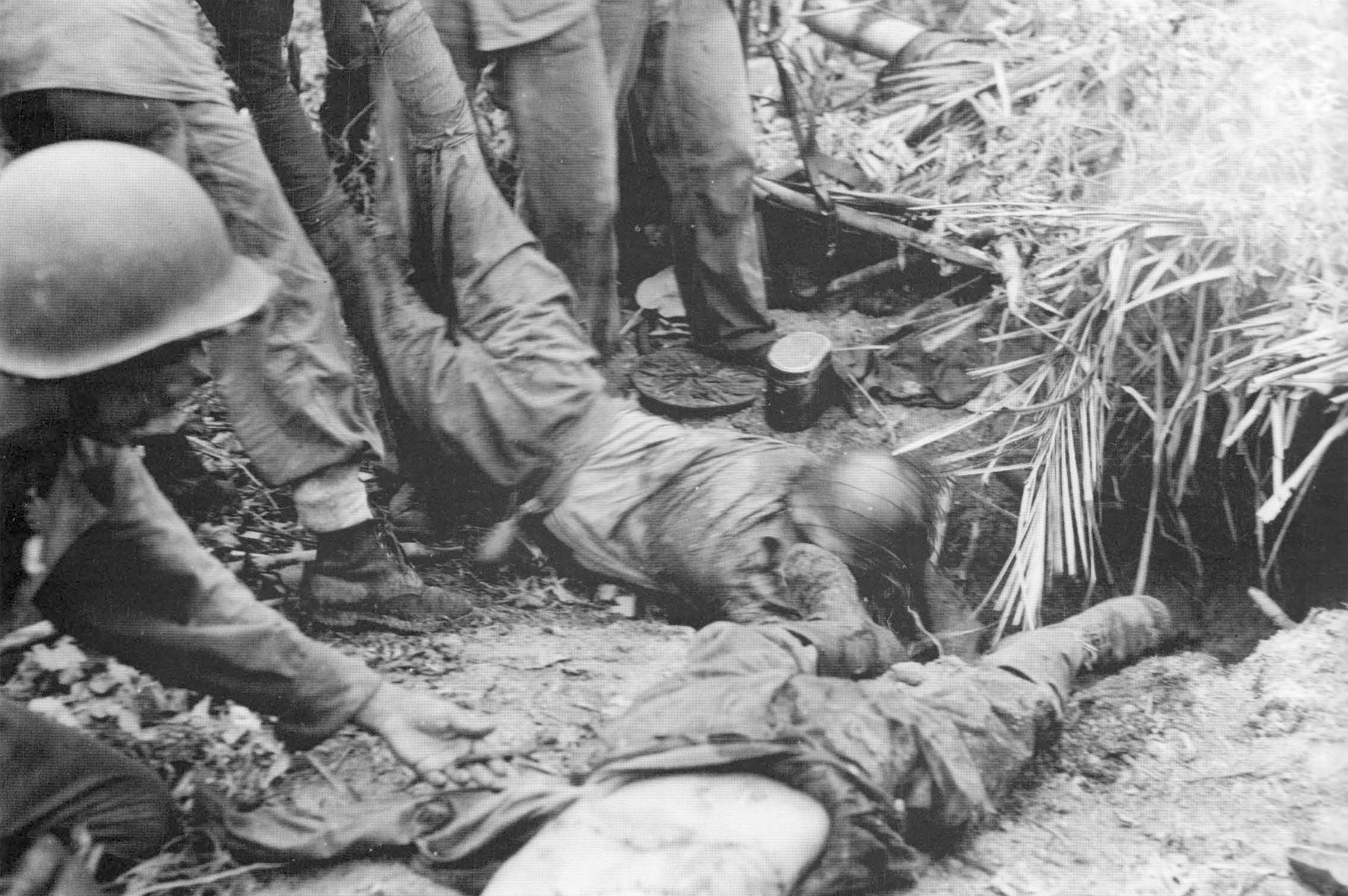 U.S. Marines drag dead Japanese soldiers from their bunker near Point Cruz on Guadalcanal in November, 1942.