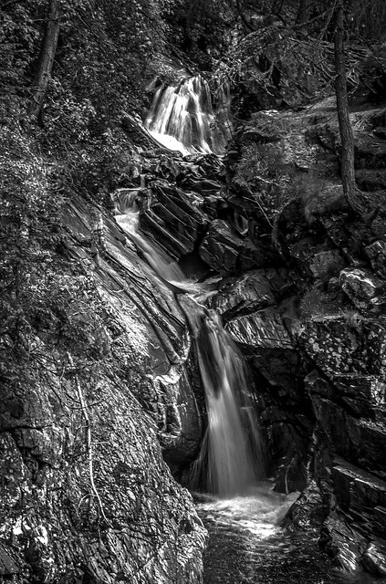 looking upstream as the water gushes in long exposure towards the Lower Bridge behind the viewpoint, falls of Bruar, fine art black & white, Perth & Kinross, Scotland, UK