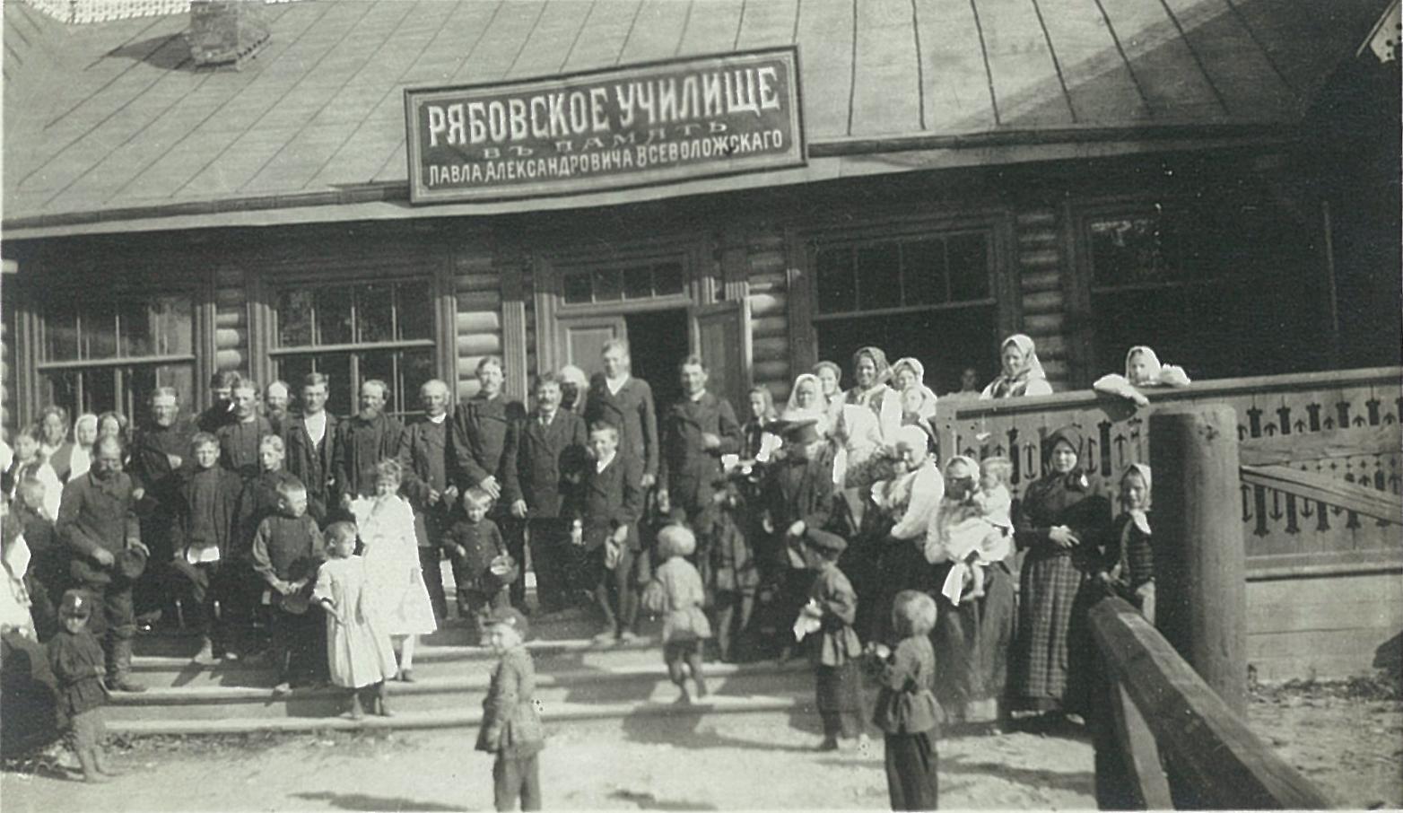 Крестьяне с детьми перед зданием Рябовского училища в память Павла Васильевича Всеволожского