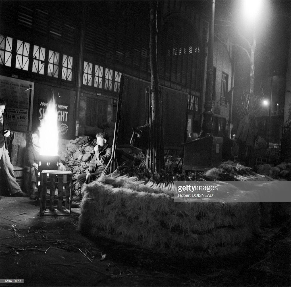 1953. Мужчины перед жаровней возле лотка с луком-пореем в ночное время в Ле-Аль