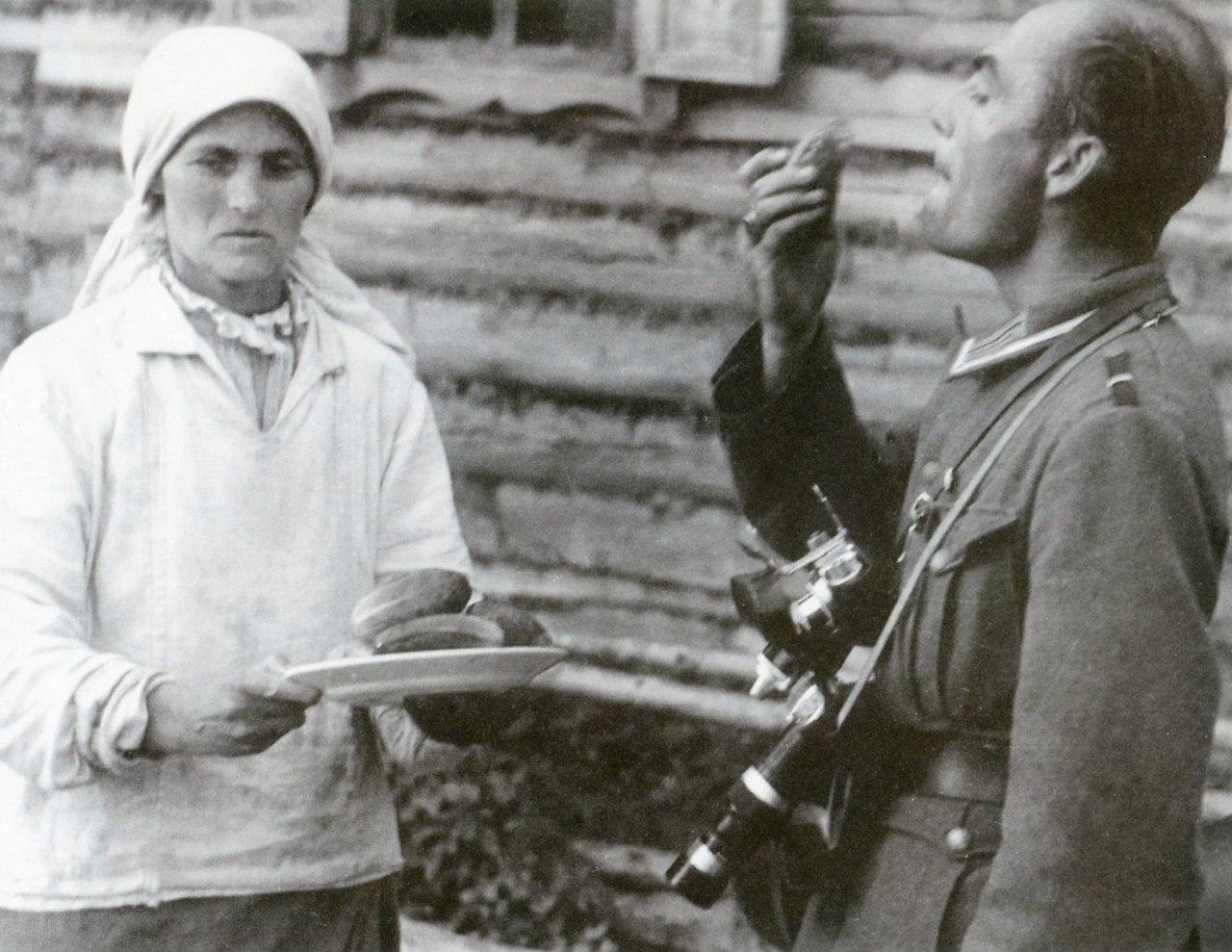 1941. Немецкий военный фотокорреспондент пробует огурцы в белорусской деревне