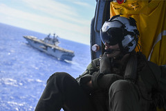 In this file photo, a Helicopter Sea Combat Control Squadron (HSC 21) crewman looks on while approaching USS Essex (LHD 2) during a vertical replenishment in July. (U.S. Navy/MC2 Adam Brock)