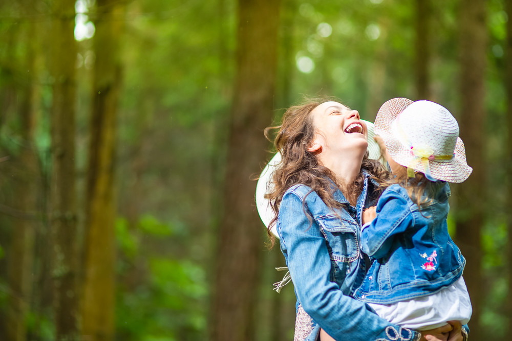 Family Ideas. portrait of Happy and Laughing Caucasian Mother with Her Little Daughter Posing Together in Green Summer Forest.