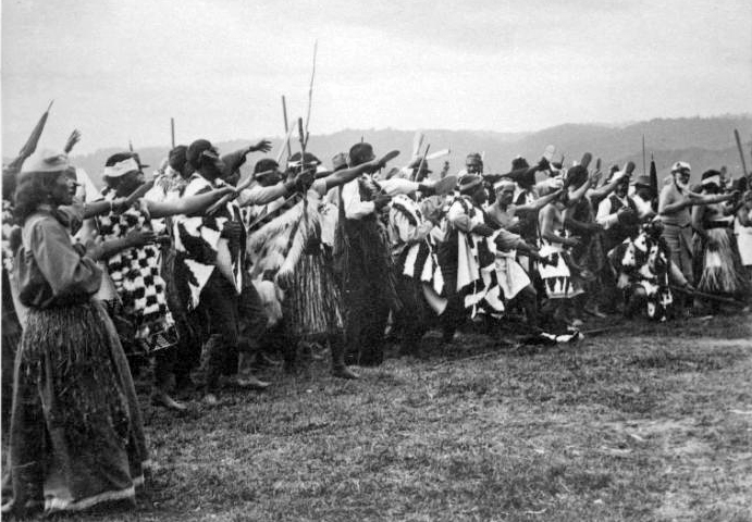 Group of Maori men and women performing a haka in Ruatoki during the visit of Lord Ranfurly and party, photographed in March 1904 by Malcolm Ross.