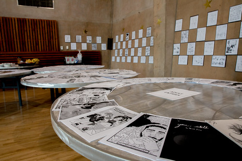 Tables with comic entries, the walls behind the tables have comic pages displayed