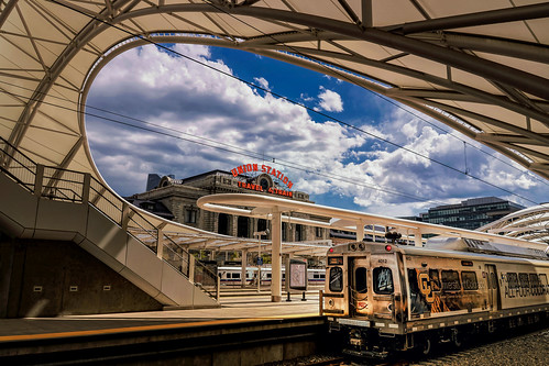 unionstation denvercolorado urban travel city rtd regionaltransportationdistrict transportationhub railwaystation railroadtransportation terminalbuilding architecture platforms canopy tracks coach carriage signage bluesky clouds cityscape cu universityofcolorado advertising livery masstransit sign travelbytrain hyundairotem emu 4012 electric stairs balast framework wires summer curvy nikond7500 sigma18300 photoshopbyfehlfarben thanksbinexo yextcolorado