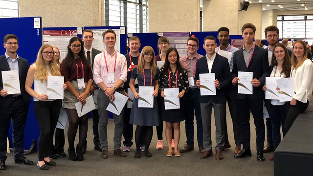 The group of winners pose in from of research posters holding up their certificates