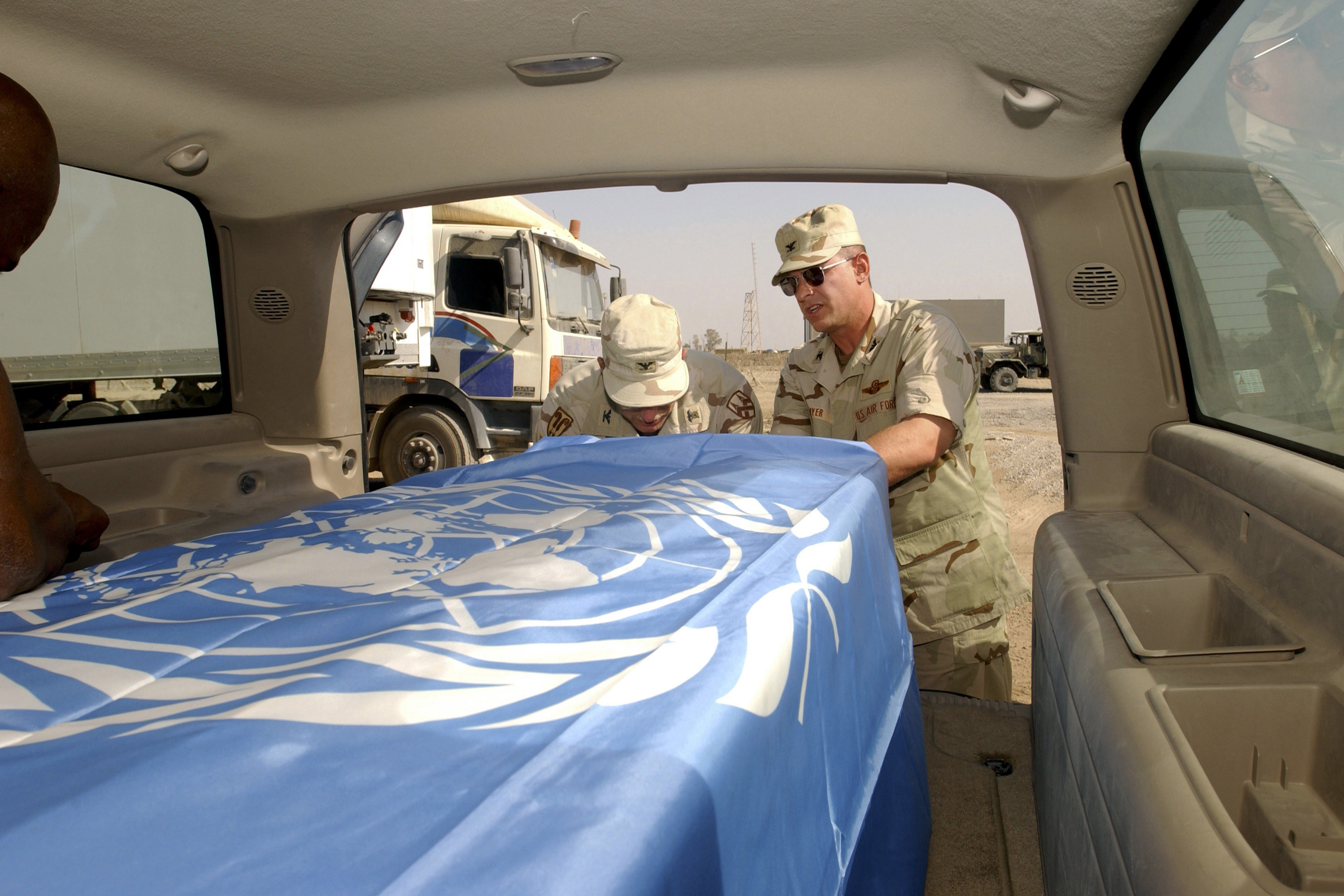 US Army (USA) Colonel (COL) Richard Dillon, Head of USA Mortuary Affairs, and US Air Force (USAF) COL Dennis Ployer, Commander, 447th Air Expeditionary Group (AEG), secure a United Nations (UN) flag over the casket of UN Chief Ambassador to Iraq, Sérgio Vieira de Mello, prior to a memorial service at the Baghdad International Airport. Sérgio Vieira de Mello was a victim of a homicide truck bombing at the United Nations Office of Humanitarian Coordinator in Baghdad, Iraq, during Operation IRAQI FREEDOM on August 19, 2003.