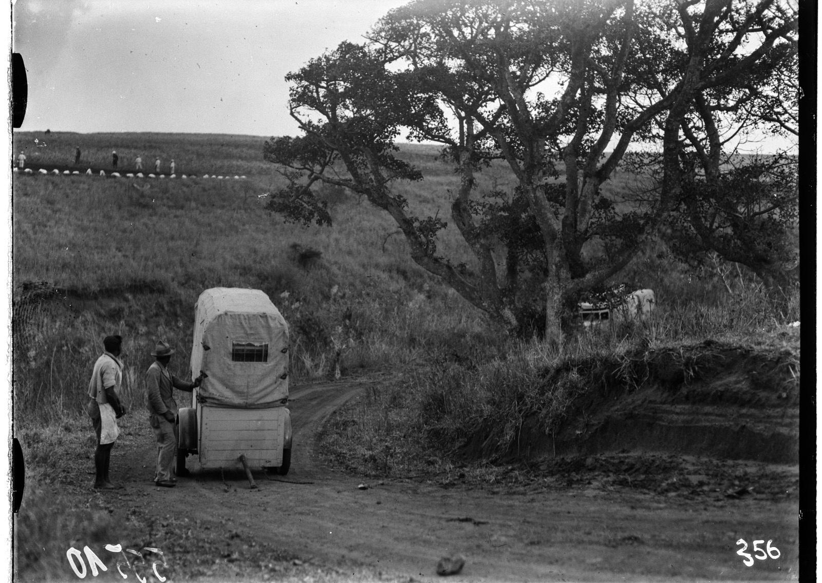 Южно-Африканский Союз. В окрестностях Претории. Два человека возле прицепа. На заднем плане участники экспедиции изучают местность