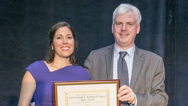Portrait of Ana Weeks and man hold her award certificate