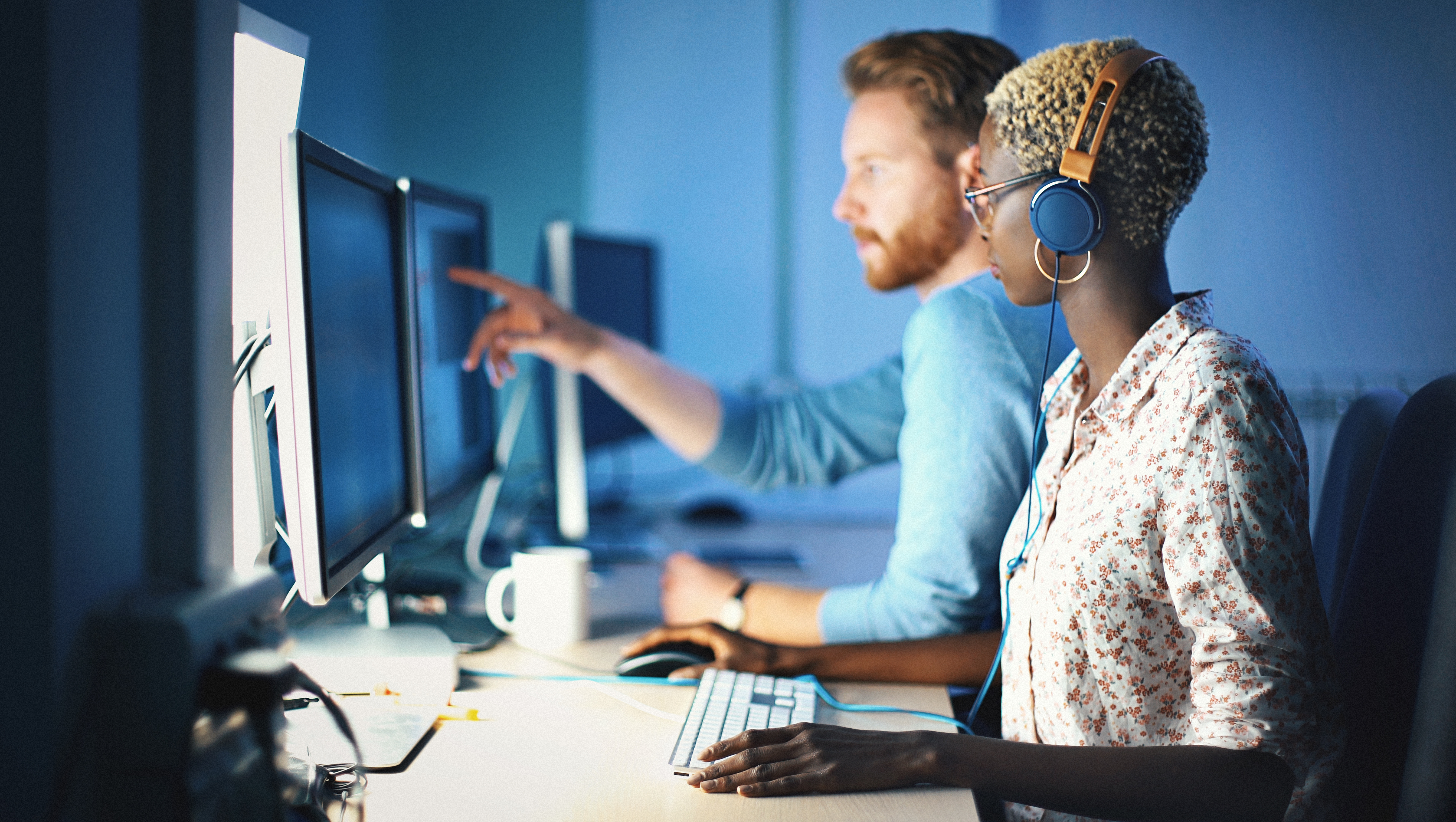 两个人坐在电脑前,看起来像是在办公.
