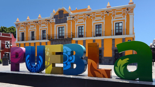 The name of the city spelled out in bright letters with a yellow building in the background in Puebla, a UNESCO Heritage site in Mexico