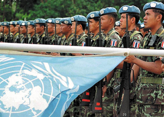 United Nations Peacekeeping Forces (UNPKF) from Thailand hold their guns up during a ceremony to mark the handover responsibility between UN peacekeeping troops and East Timor armed forces in Los Palos, East Timor, July 23, 2002. East Timor's army replaced UN peacekeepers in one district of the new nation -- the first step in a 20-month handover which will see the blue berrets bow out. (FILM) AFP PHOTO/Antonio DASIPARU