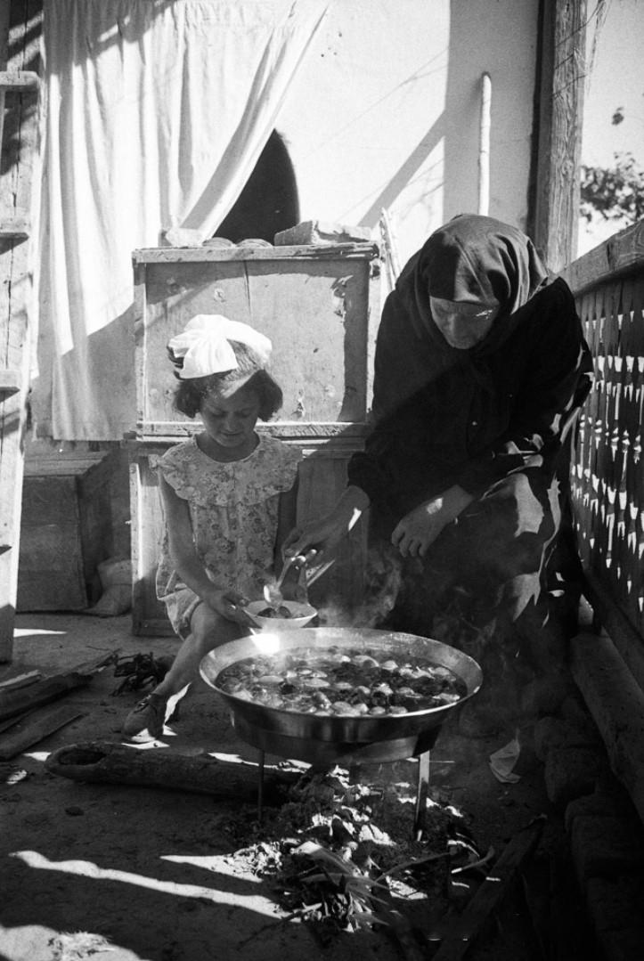 Пожилая женщина в национальной одежде готовит с внучкой чахохбили в доме на углях