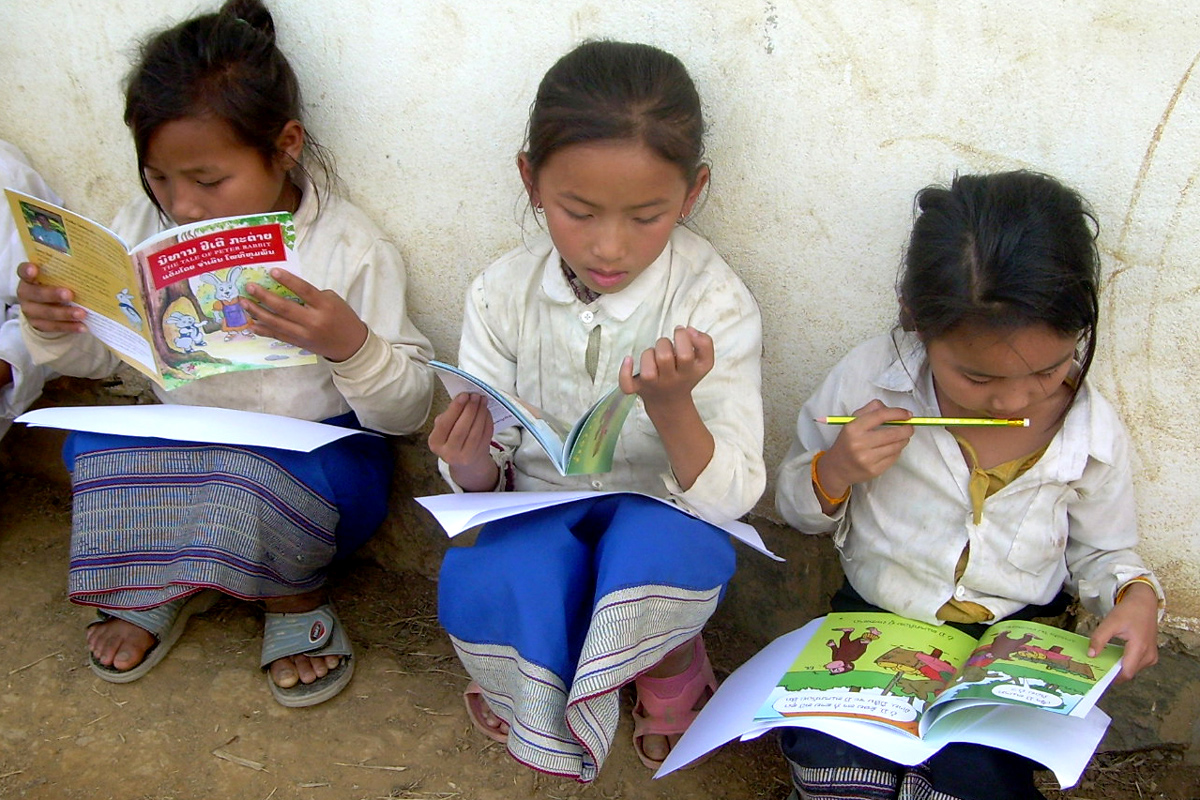 Three Lao girls sit outside their school, each absorbed in reading a book. This photo was taken after a rural school book party by Big Brother Mouse, a publishing and literacy project in Laos, which provides many children with their very first books. Photo taken on December 10, 2009..
