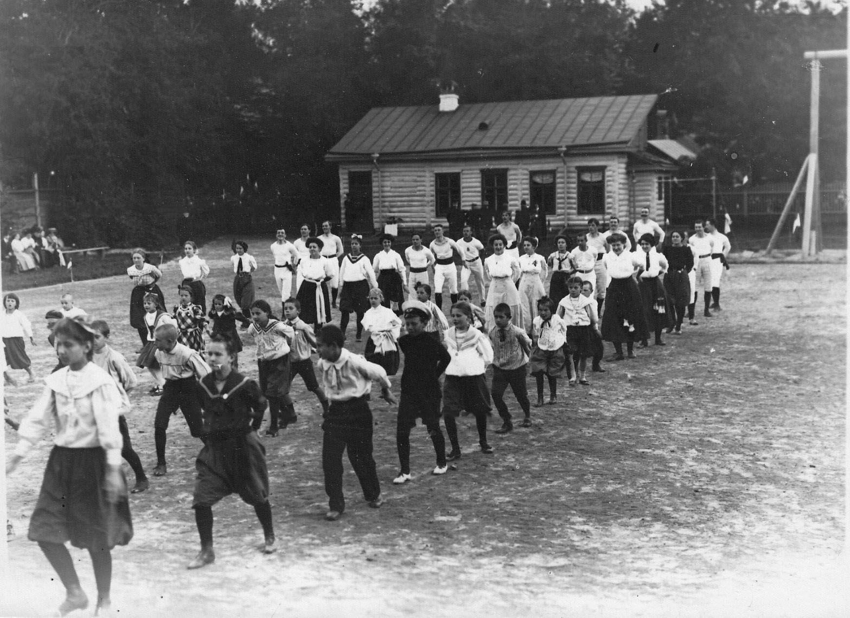 Группа детей и взрослых членов Гимнастического общества «Пальма» на занятиях гимнастикой