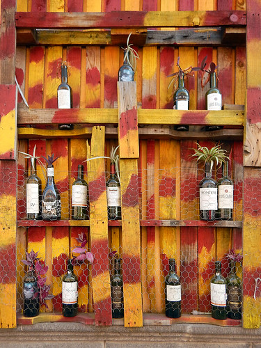 Wine bottles used to root cuttings in a dark red & yellow cupboard in Puebla, a UNESCO Heritage site in Mexico