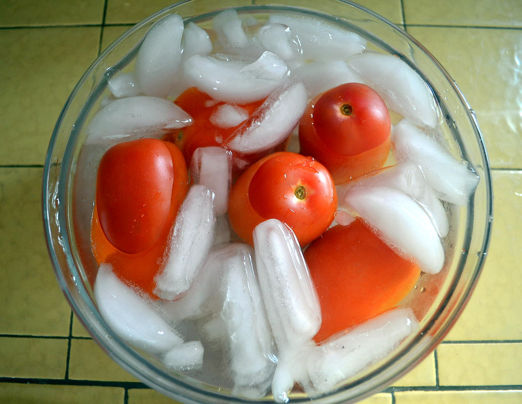 After tomatoes are quickly blanched, place them in an ice cold water bath to stop cooking.