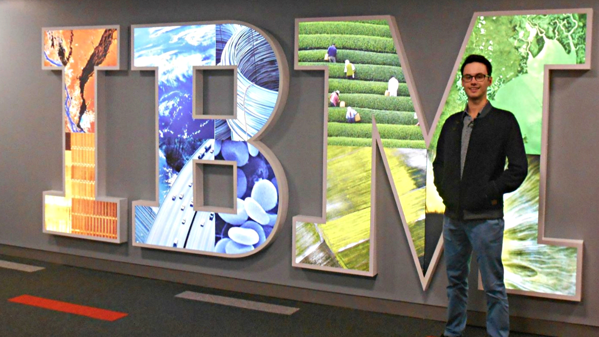A placement student standing next to the IBM sign