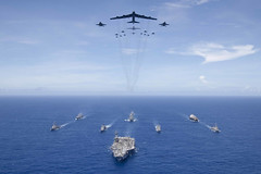 PHILIPPINE SEA (Sept. 17, 2018) USS Ronald Reagan (CVN 76) leads a formation of Carrier Strike Group 5 ships as U.S. Air Force and U.S. Navy aircraft, led by a B-52 Stratofortress long-range bomber pass overhead during Valiant Shield 2018. The biennial, U.S. only, field-training exercise focuses on integration of joint training among the U.S. Navy, Air Force, Army and Marine Corps. This is the seventh exercise in the Valiant Shield series that began in 2006. (U.S. Navy photo by Mass Communication Specialist 3rd Class Erwin Miciano)