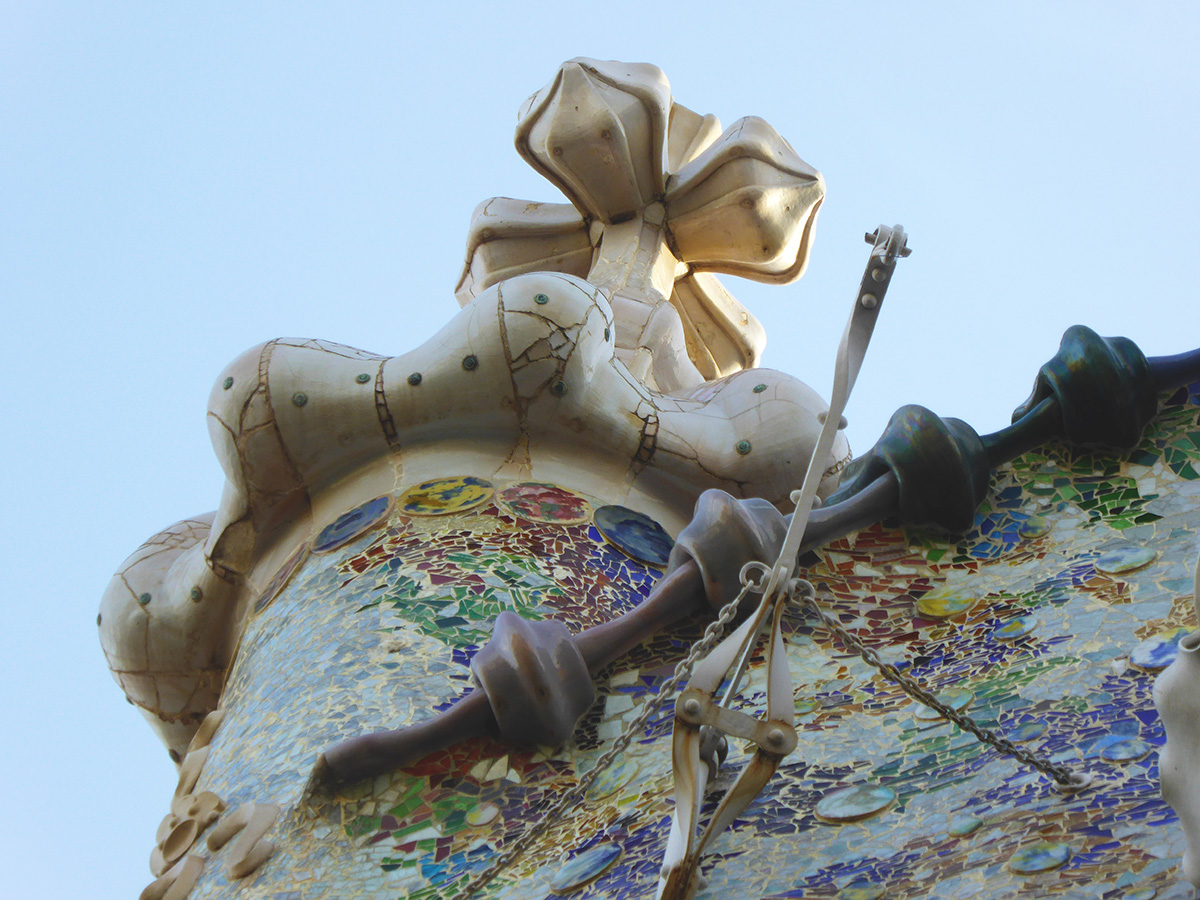 A view of the top tower and architectural adornment of Casa Batllo, one of the buildings designed by Antoni Gaudí i Cornet which has been given UNESCO historical places status