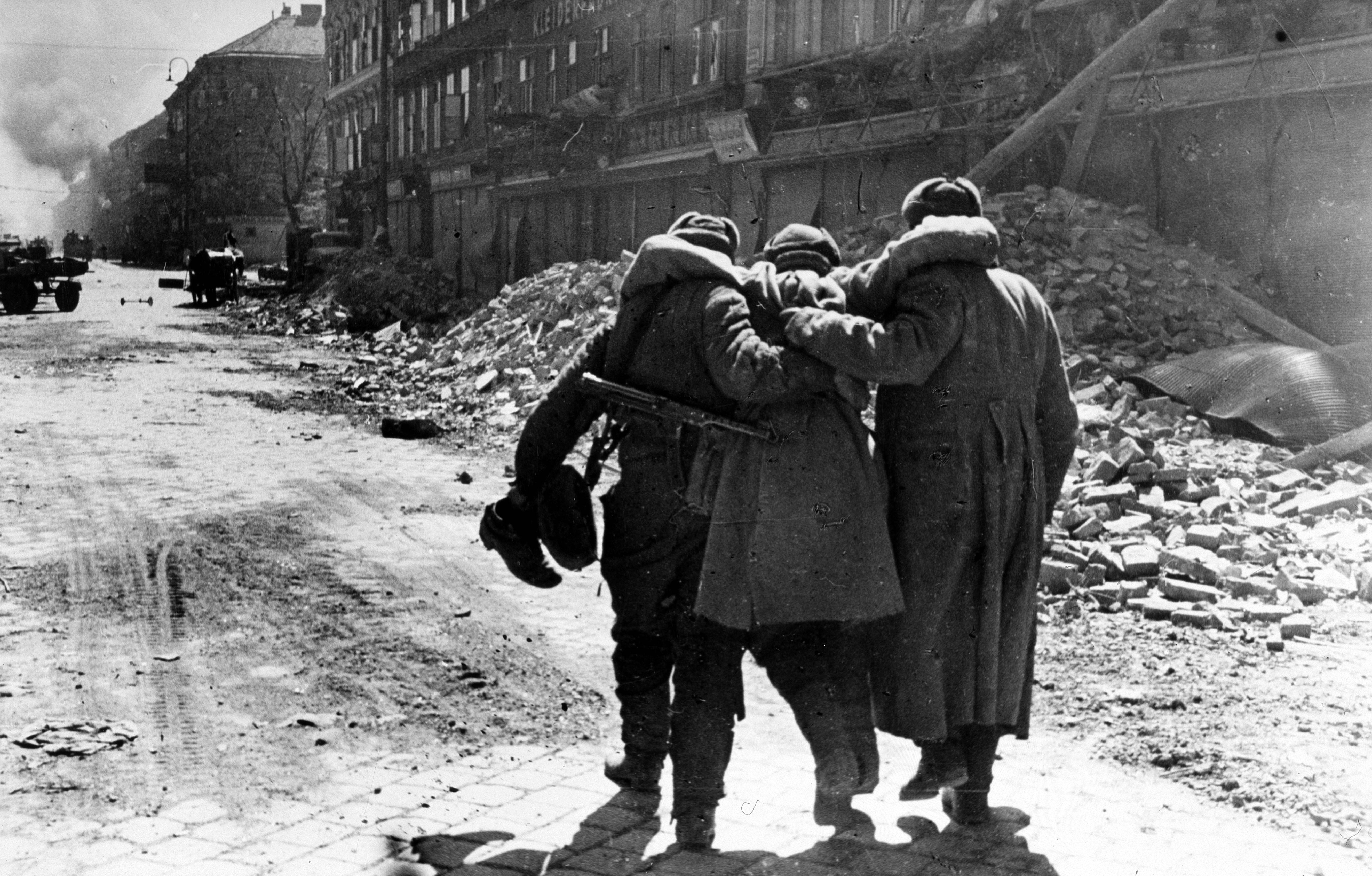 1945. Красноармейцы помогают идти раненому товарищу во время боев за Вену